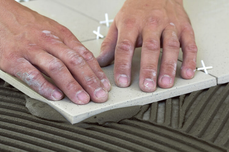 workers hands with ceramic tiles and tools for tiler